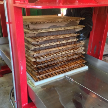 When all the blankets are full, they're pulled under the hydraulic press.