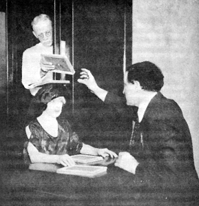 Houdini, his wife, and an assistant demonstrate a method of switching slates over a sitter's head that would be performed in a dark room during a seance.
