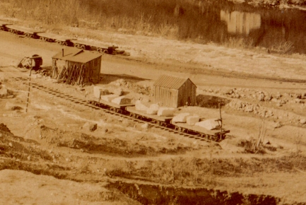 Large chunks of stone on flat railcars, waiting to be transported through the tunnel to the face of the dam.