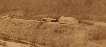 Detail showing some construction buildings on the other side of the river below the dam