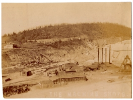 The machine shops below the dam (where the park is today) with the temporary suspension bridge over the river in the background. The house on the hill was used as the construction office.