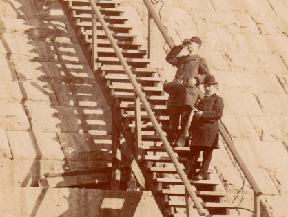 Detail showing the man higher up the stairs looking through a pair of binoculars